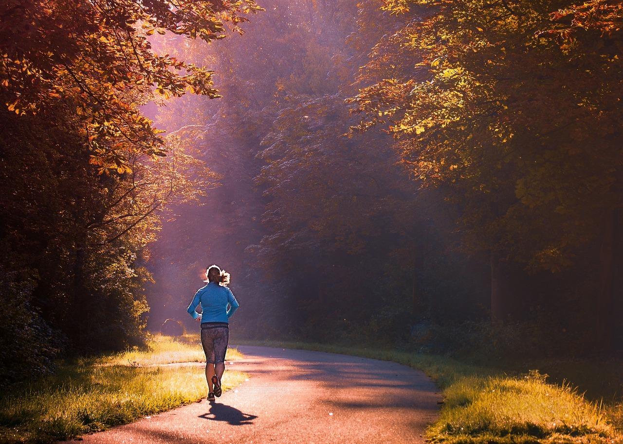 Vrouw in een blauw jack aan het hardlopen in een bos