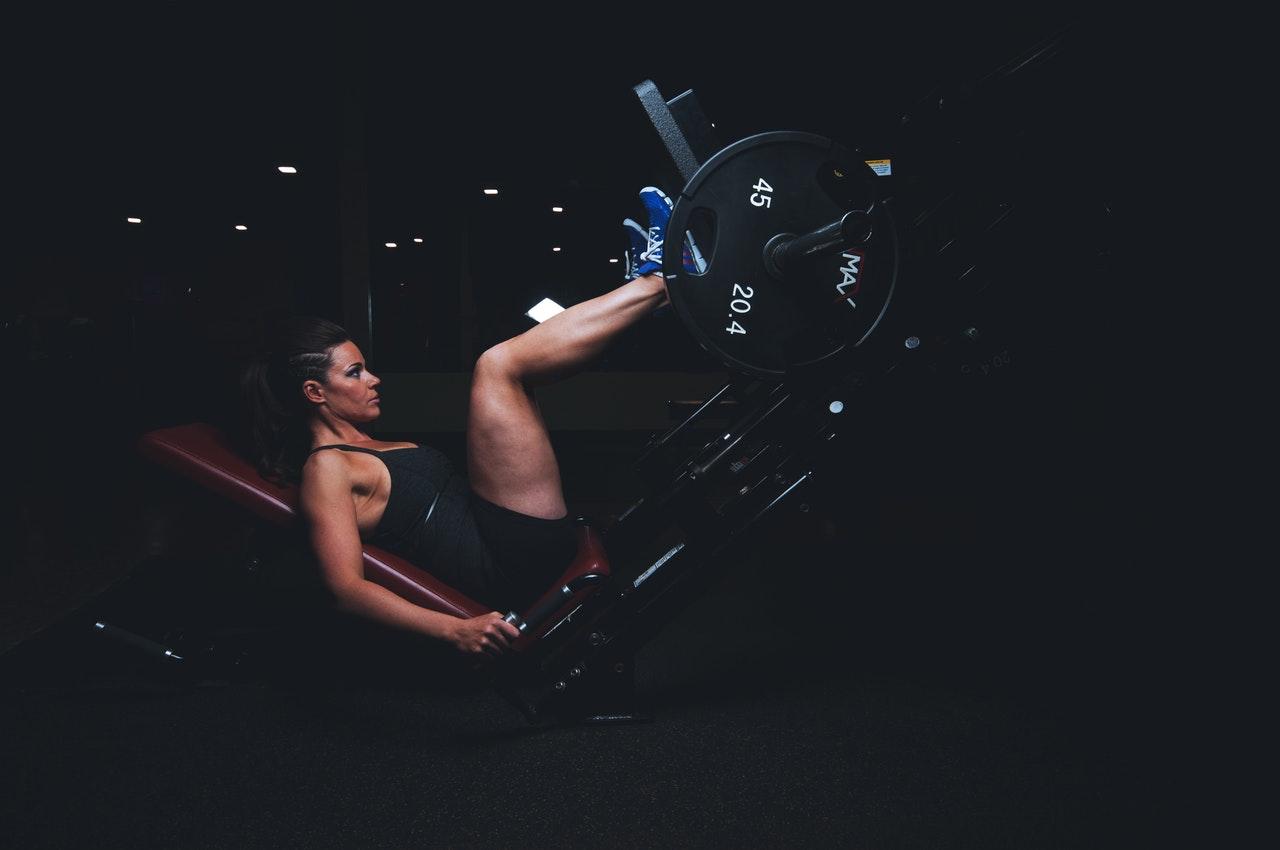 vrouw in sportkleding op een leg press machine