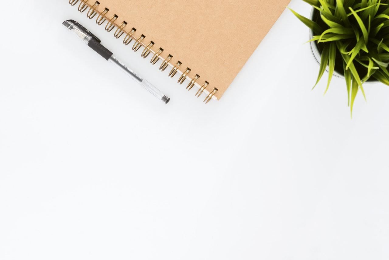 notitieblok om trainingsschema te maken naast een plant en pen met een blanco achtergrond