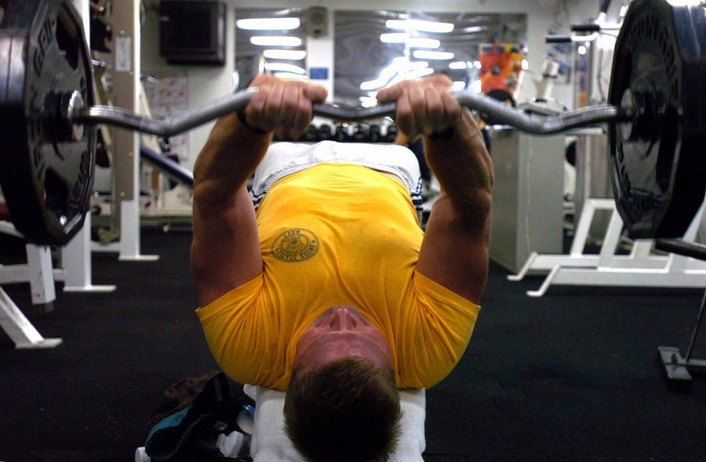 man in geel t-shirt in sportschool die triceps aan het trainen is met een ez barbell