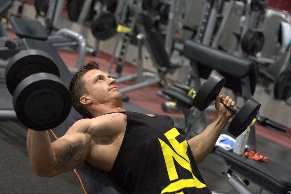 bovenkant borst trainen in de sportschool door een man in een zwarte tanktop met dumbbells