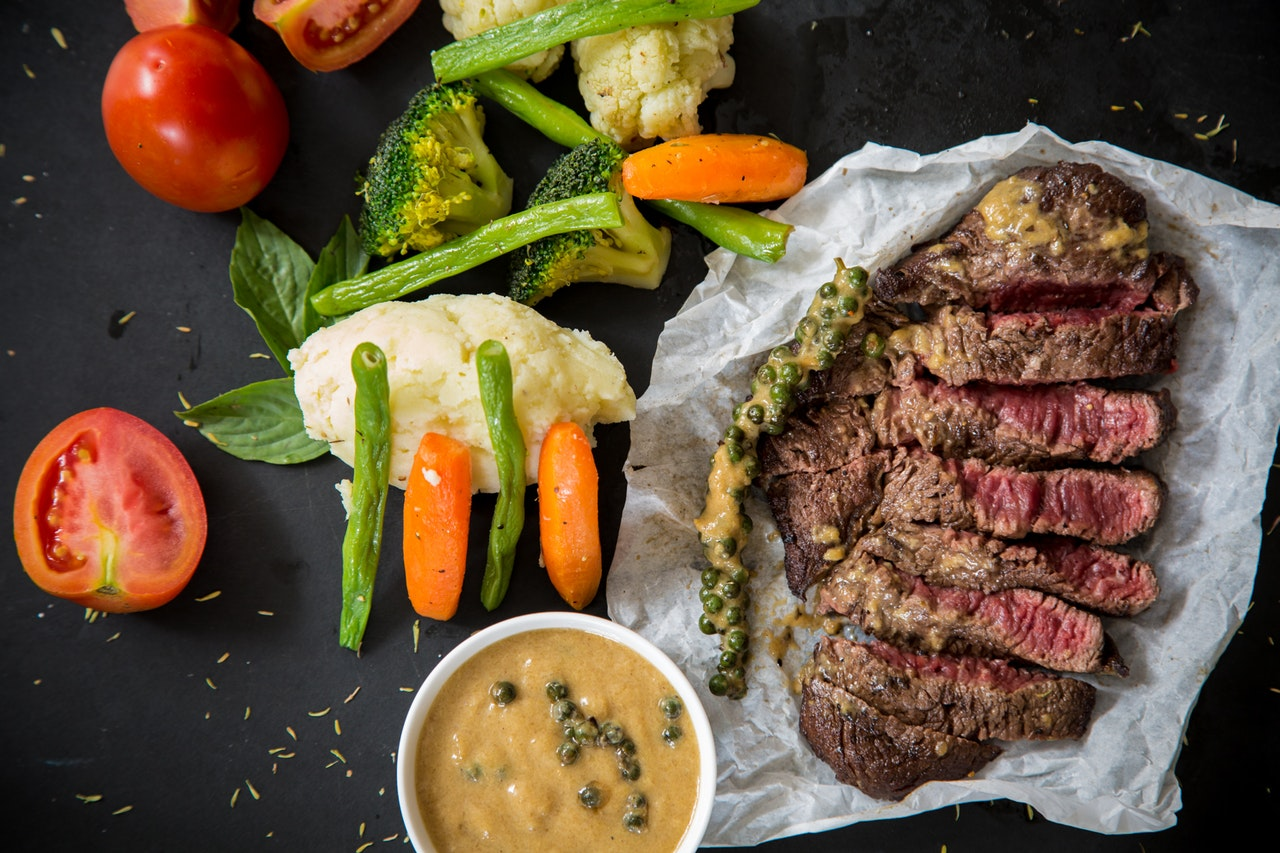 Een tafel met daarop veel voeding met ijzer, zoals steak en groenten