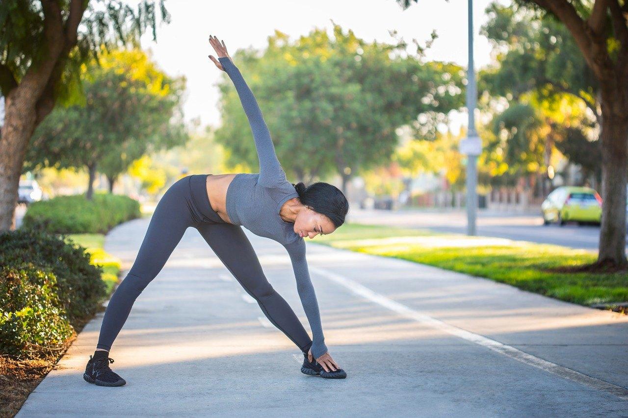 sportieve vrouw in grijze kleding op straat aan het rekken tijdens een warming up voor het hardlopen