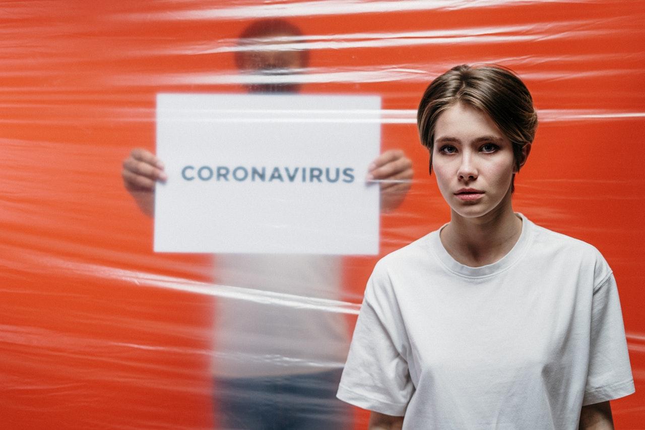 twee mensen met een stuk papier met coronavirus geschreven