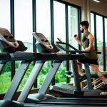 man aan het sporten met spierpijn op de loopband in de sportschool