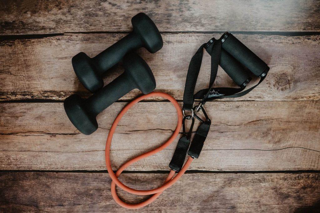 thuis fitnessen met dumbbells en weerstandsbanden
