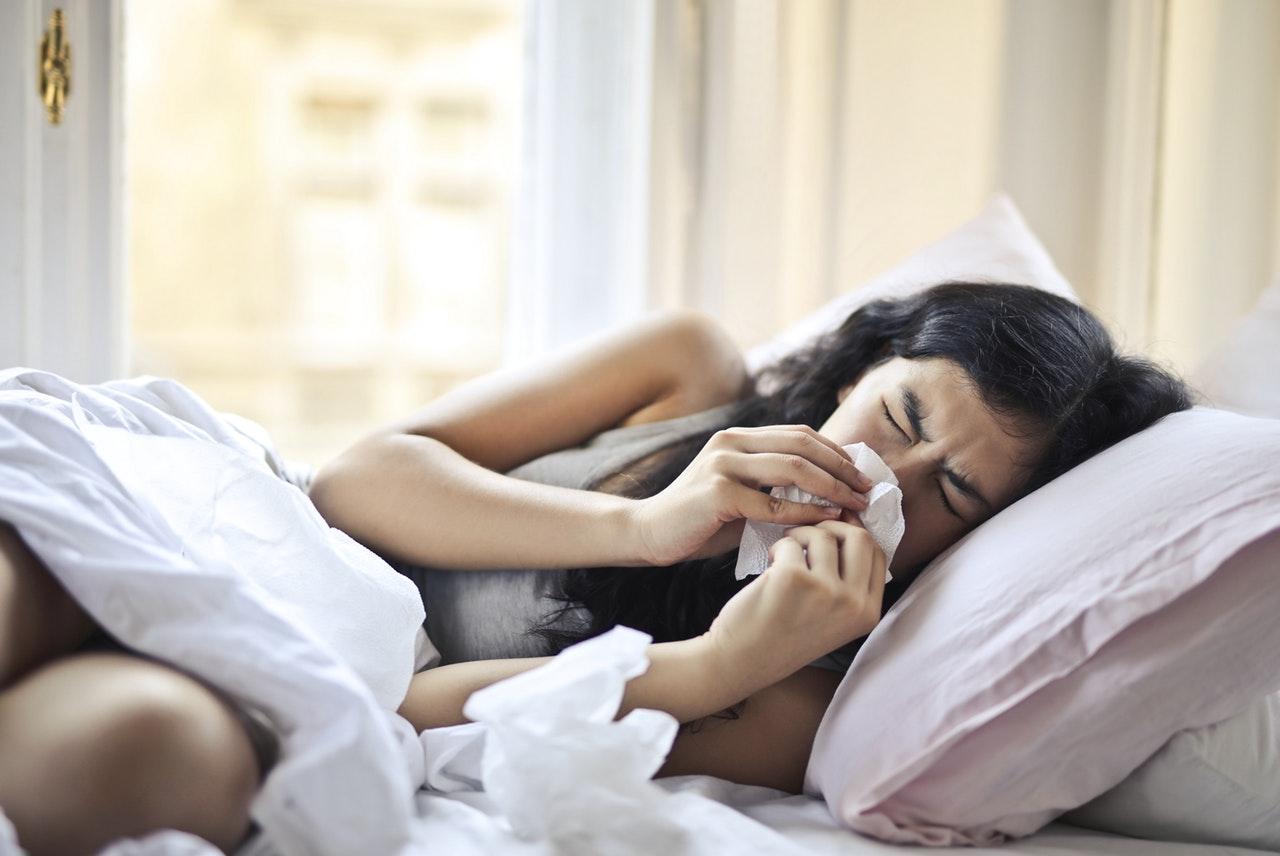 Vrouw snuit haar neus en ligt ziek op bed en wilt haar weerstand verhogen
