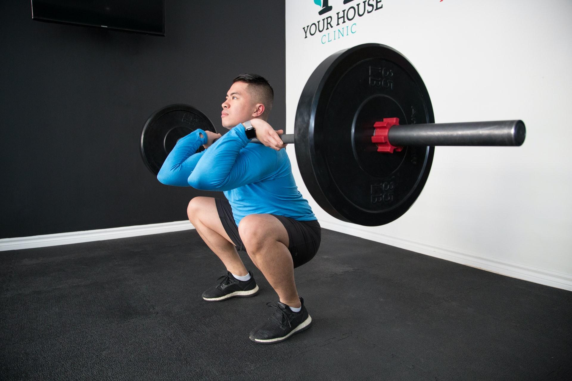 front squat door een man met blauw shirt in de sportschool