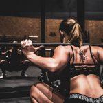 spiergroepen trainen door een vrouw die een squat uitvoert in de sportschool
