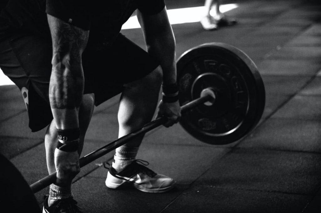 man wil sterker worden door het doen van een oefening met een barbell in de sportschool