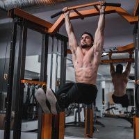 hanging leg raises door een man zonder shirt in de sportschool