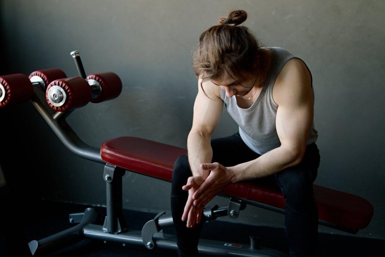 motivatie om te sporten is laag bij persoon met knotje in grijs hemd