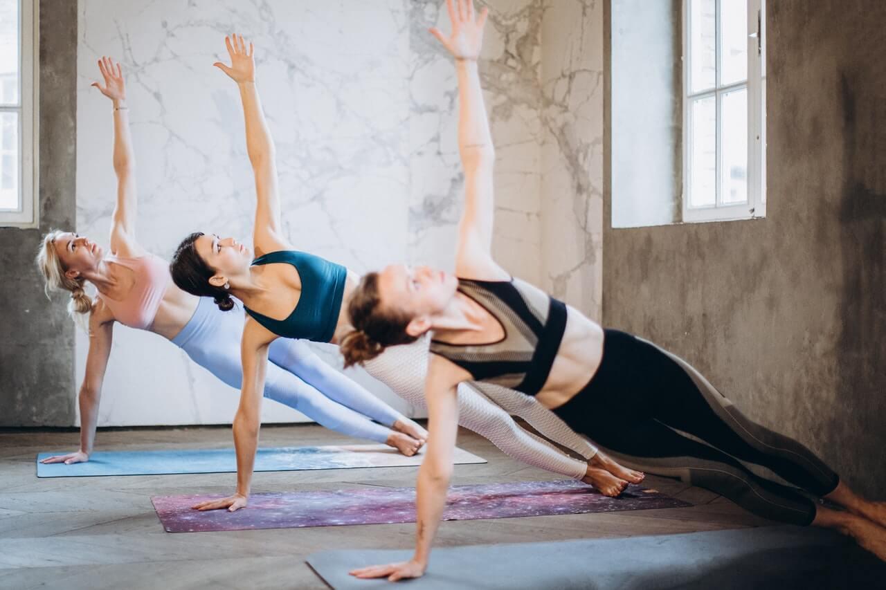 side plank door drie vrouwen in een sportzaal