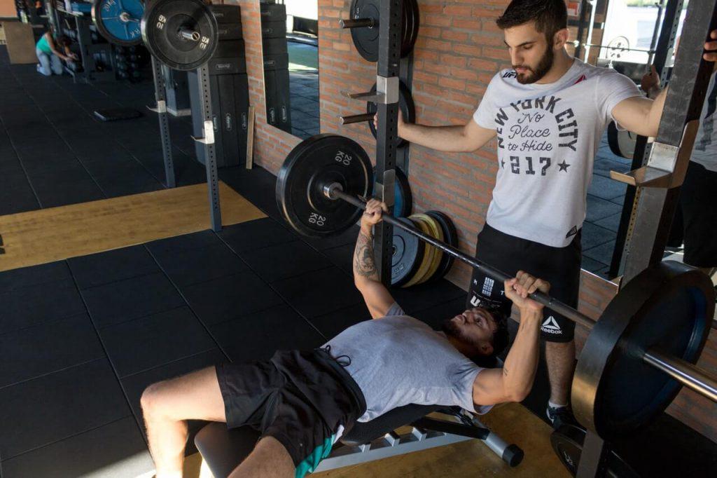 excentrisch trainen bij het bankdrukken door twee jonge mannen in een sportschool