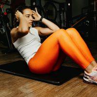 sit-ups door een vrouw in oranje legging