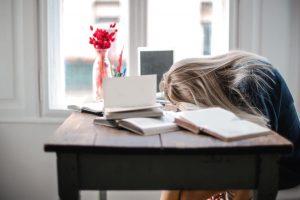 slaaptekort door een vrouw die aan het studeren is aan haar bureau
