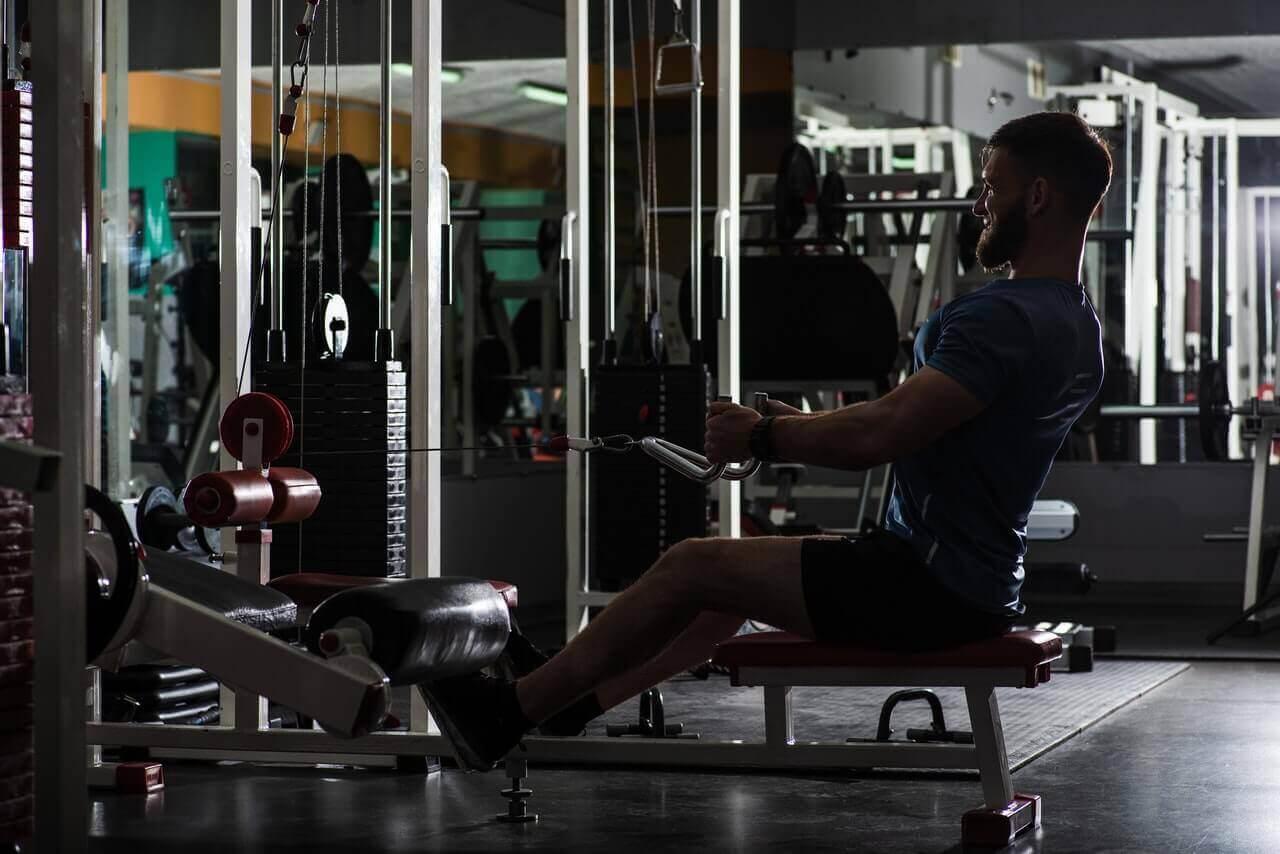 seated cable row in de sportschool door een man