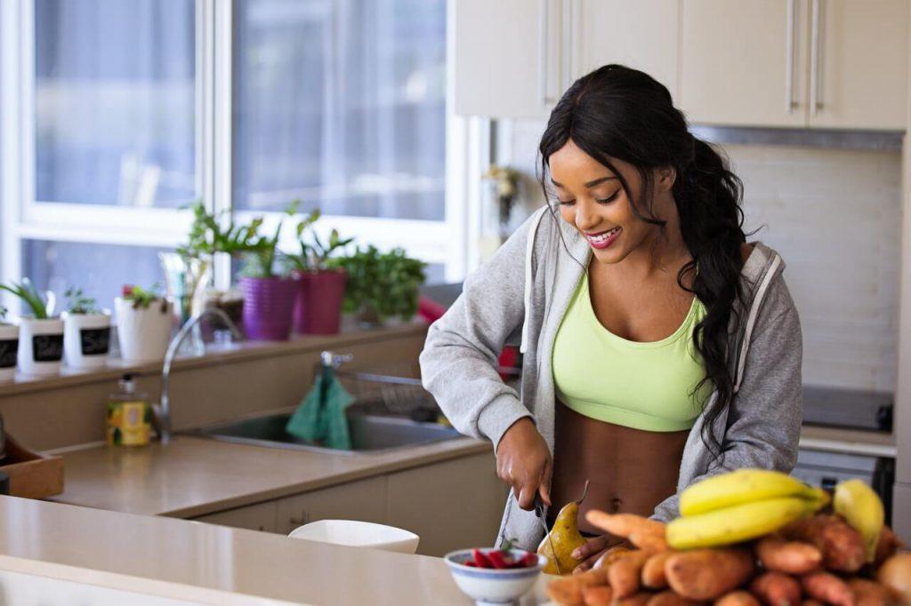 Een jonge vrouw met gezond gewicht in de keuken