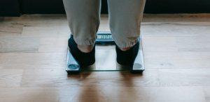 persoon met grijze broek en zwarte sokken die graag wilt afvallen zonder sporten op een weegschaal