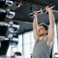 dumbbell shoulder press door een man met grijs hemd in de sportschool