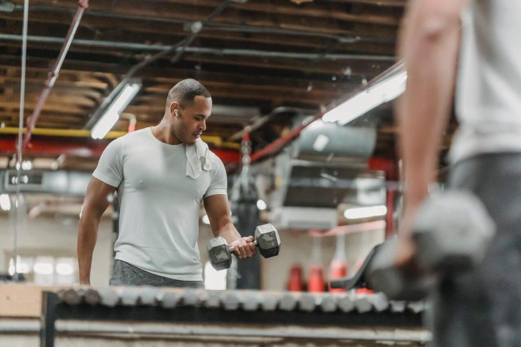 Fitness tips van een man in grijs shirt in de sportschool die biceps traint met dumbbells