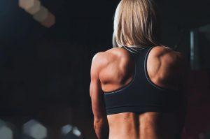 vrouw in sportschool tijdens het trainen van trapezius