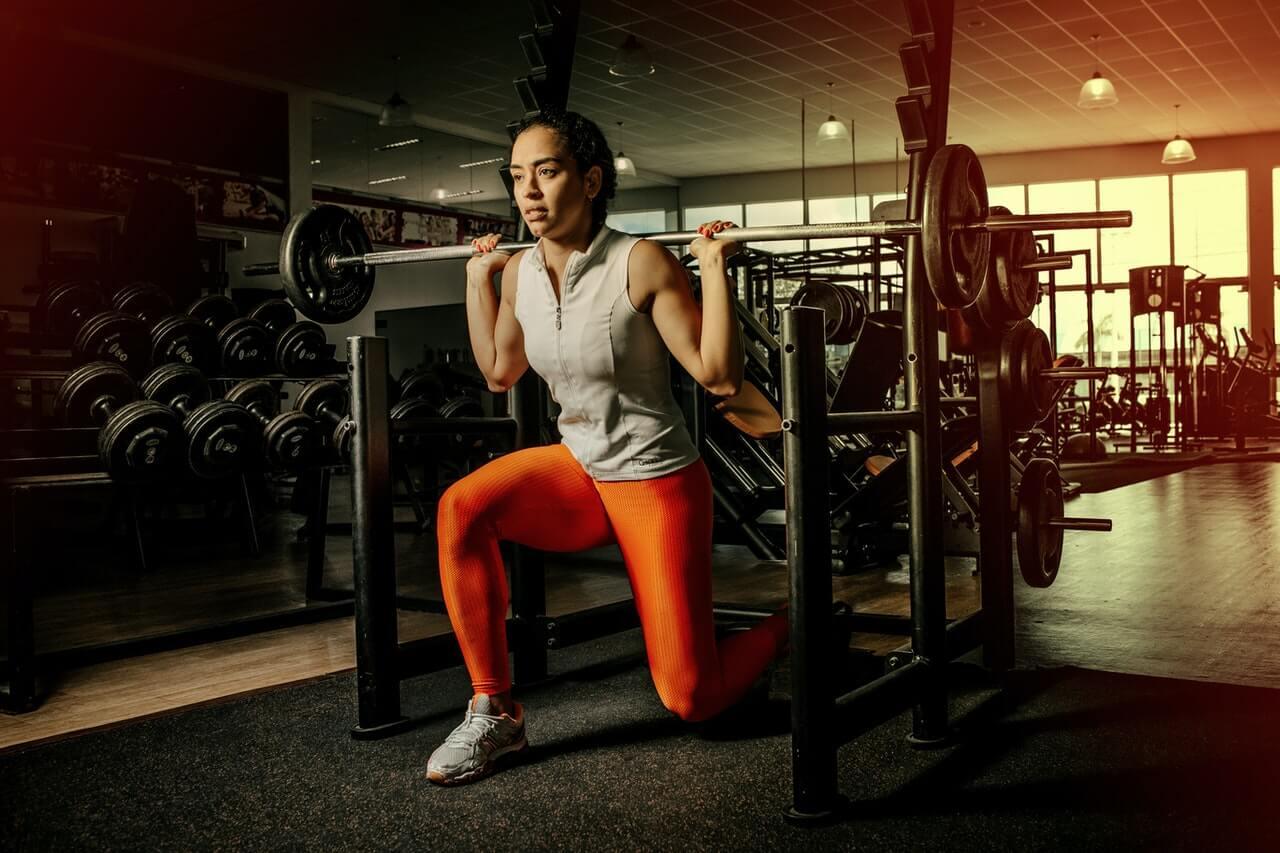 split squat in de sportschool door een vrouw met oranje legging