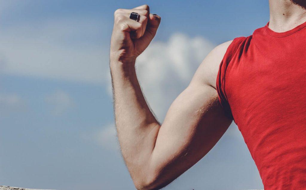 muscle memory bij een man met rood shirt die zijn biceps aanspant