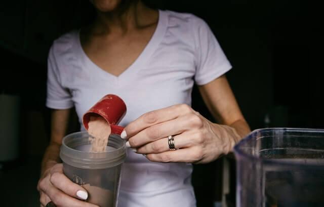 Vrouw in wit shirt ontdekt de voordelen van eiwitshakes