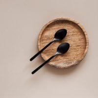 sporten op lege maag door leeg houten bord met zwarte lepels