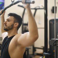 lat pulldown door een man in hemd in de sportschool