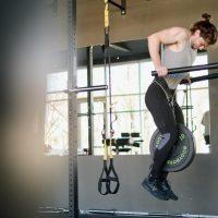 triceps dips door een man in grijs hemd in een sportschool