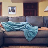 persoon kampt met symptomen van bloedarmoede en ligt ziek op een grijze bank onder een blauw deken